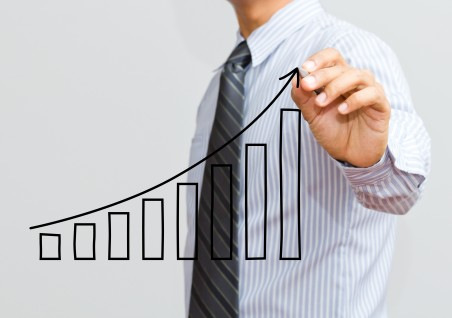 Businessman drawing upwards curve bar chart